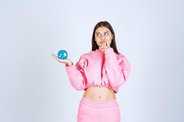미니 글로브를 들고 생각하고 분홍색 잠옷 소녀.