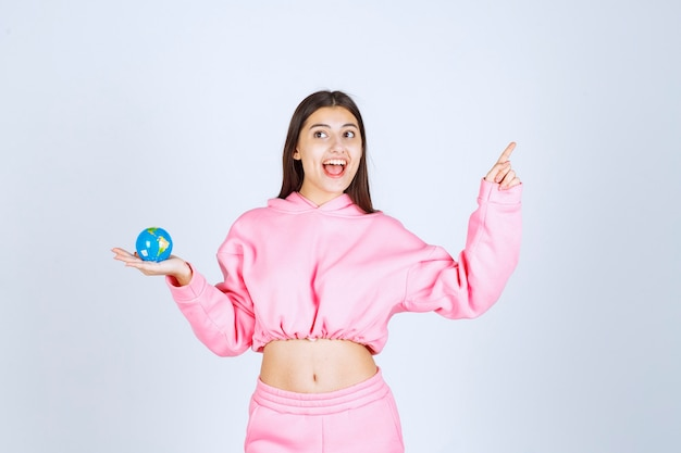 どこか上を指しているミニ地球儀を持っているピンクのパジャマの女の子。