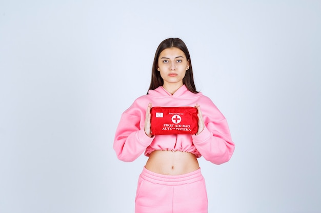 赤い応急処置キットを持ってそれを宣伝するピンクのパジャマの女の子。