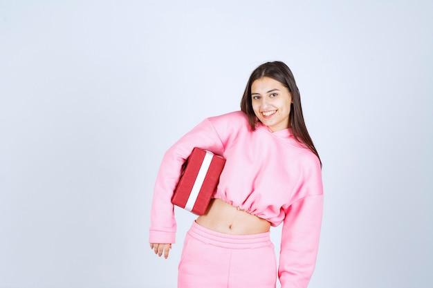 Девушка в розовой пижаме держит красную прямоугольную подарочную коробку и выглядит довольной.