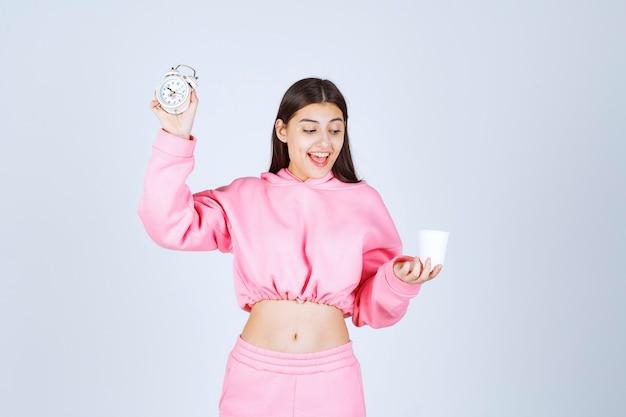 目覚まし時計とコーヒーを持っているピンクのパジャマの女の子。