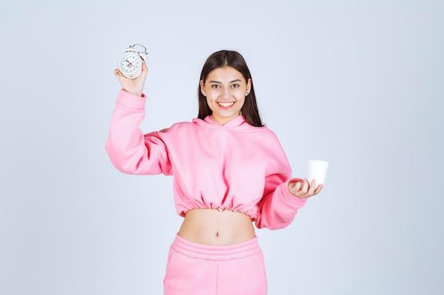 Девушка в розовой пижаме держит будильник и чашку кофе.