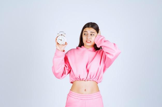 알람 시계를 들고 분홍색 잠옷을 입은 소녀가 소음 때문에 방해받습니다.