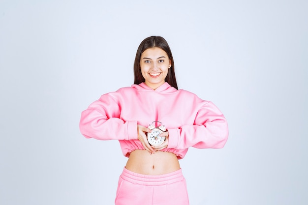 Девушка в розовой пижаме держит будильник и продвигает его как продукт.