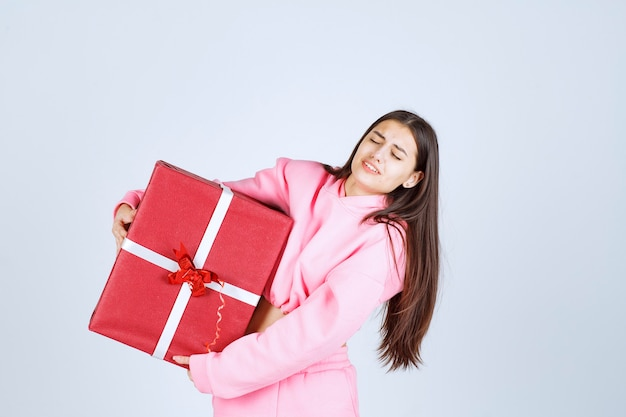 큰 빨간 선물 상자를 껴안고 웃고 분홍색 잠옷 소녀.
