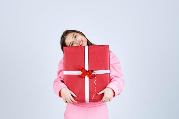 大きな赤いギフトボックスを抱きしめて笑っているピンクのパジャマの女の子。