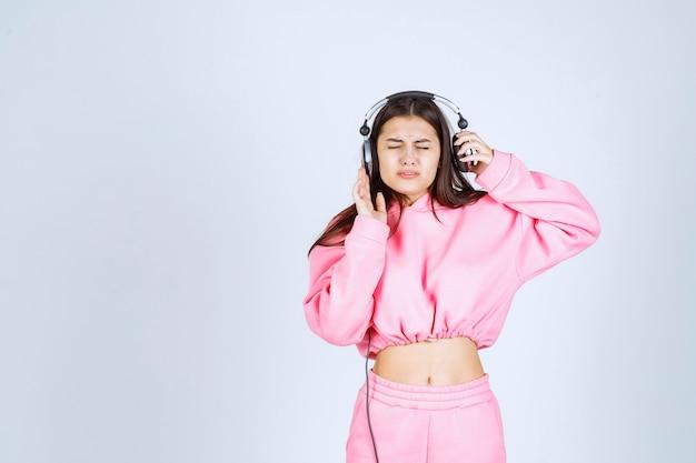 분홍색 잠옷을 입은 소녀는 헤드폰을 듣고 음악을 좋아하지 않습니다.