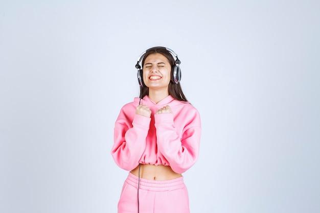 Девушка в розовой пижаме слушает наушники и веселится. фото высокого качества