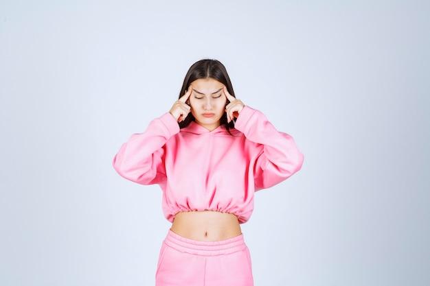 분홍색 잠옷을 입은 소녀는 혼란스럽고 의심스러워 보입니다.