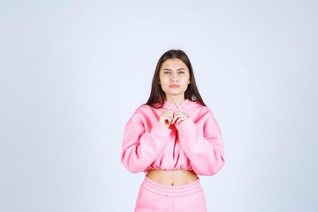 Девушка в розовой пижаме выглядит растерянной и сомнительной