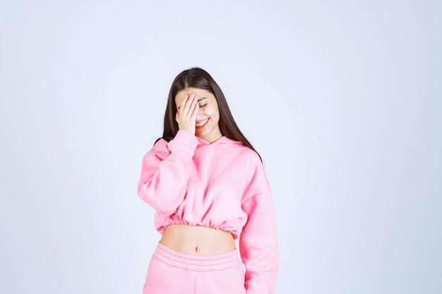 ピンクのパジャマを着た女の子は混乱して思慮深く見えます。