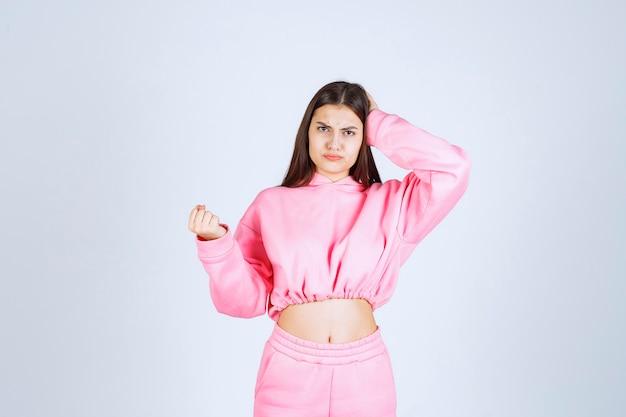ピンクのパジャマを着た女の子は混乱して思慮深く見えます