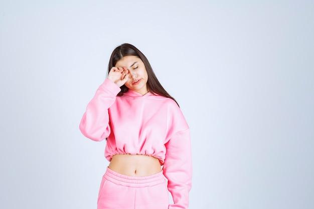 Девушка в розовой пижаме выглядит сонной