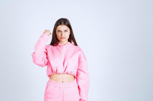 ピンクのパジャマを着た女の子はスポーティーに見え、拳を見せます