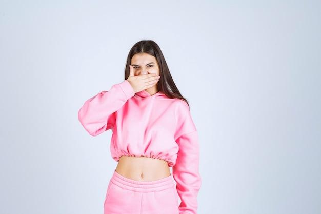 Девушка в розовой пижаме выглядит усталой и сонной