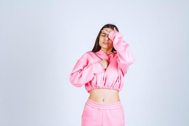 ピンクのパジャマを着た女の子は疲れて眠そうに見えます