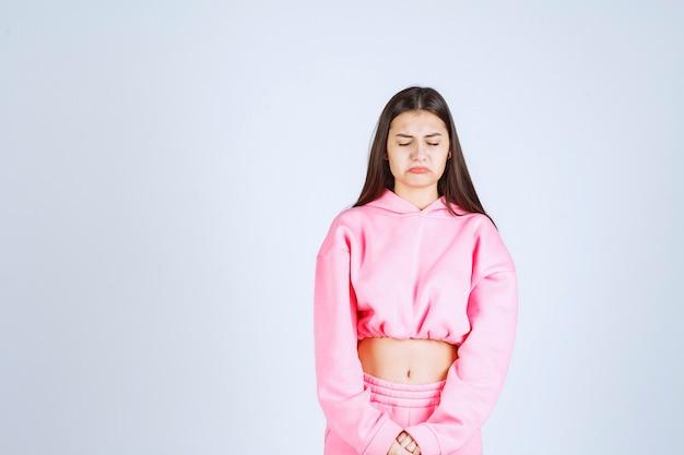 非常に攻撃的で怒った顔をしているピンクのパジャマの女の子