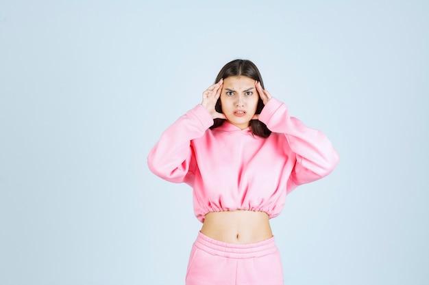 非常に攻撃的で怒った顔をしているピンクのパジャマの女の子 無料写真