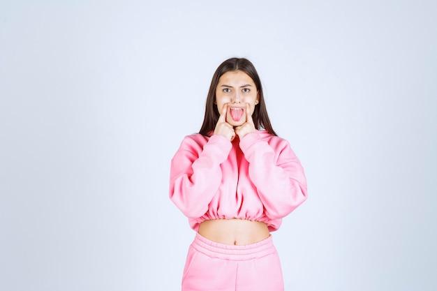 Девушка в розовой пижаме, указывая на ее рот