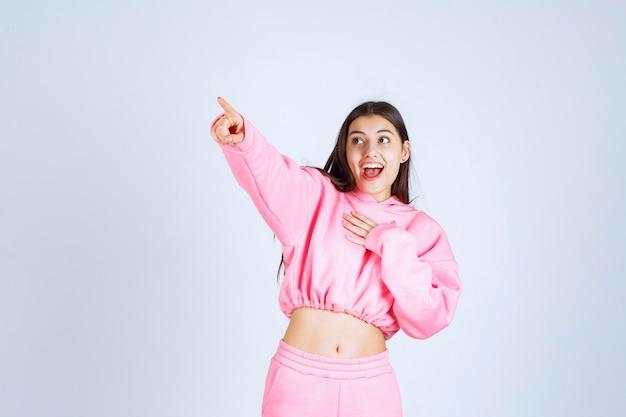 왼쪽에 뭔가 가리키는 분홍색 잠옷 소녀
