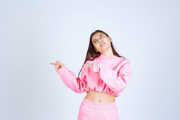 Девушка в розовой пижаме, указывая на что-то слева