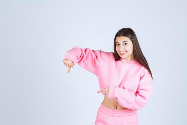 아래를 가리키는 분홍색 잠 옷 소녀