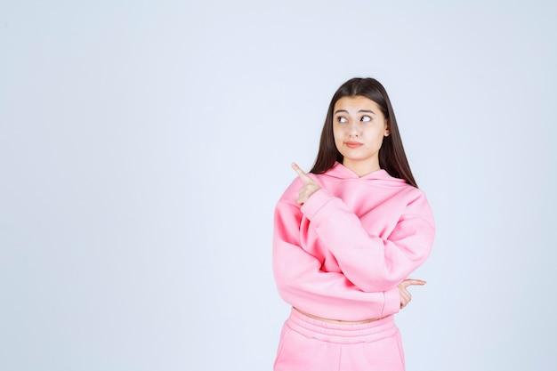 左側を指すピンクのパジャマの女の子