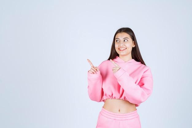왼쪽을 가리키는 분홍색 잠 옷 소녀