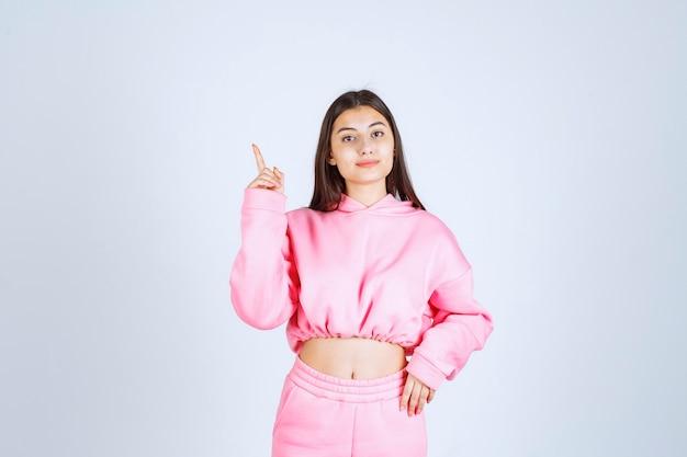 감정적 인 얼굴로 위층을 가리키는 분홍색 잠옷 소녀