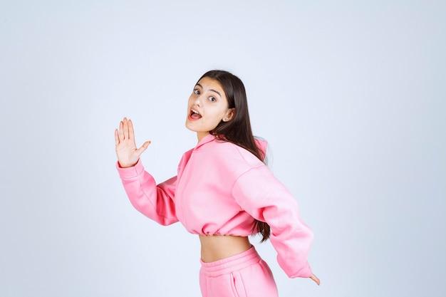 場所から走っているピンクのパジャマの女の子