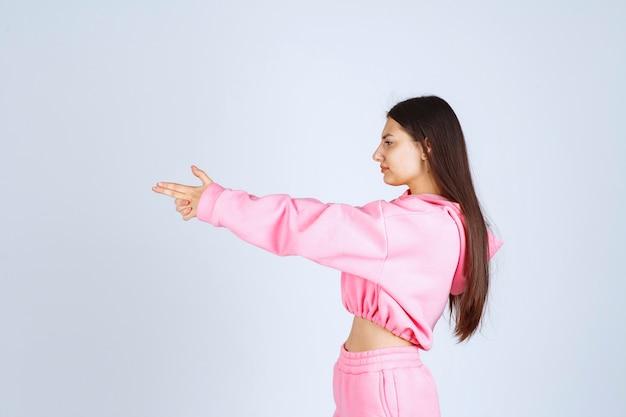 손에 총 기호를 보여주는 분홍색 잠 옷에있는 여자
