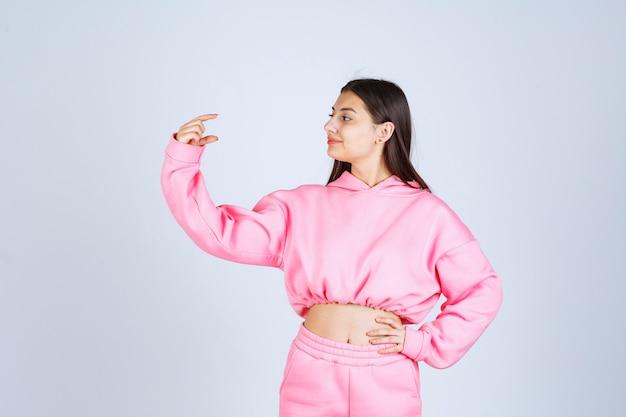 제품의 양을 보여주는 분홍색 잠옷 소녀