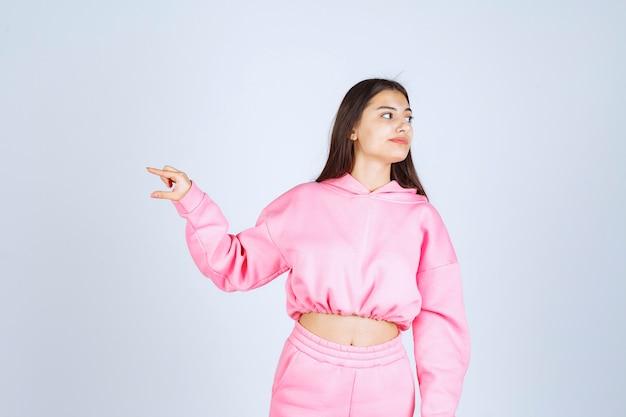 제품의 예상 수량 또는 크기를 보여주는 분홍색 잠옷을 입은 소녀