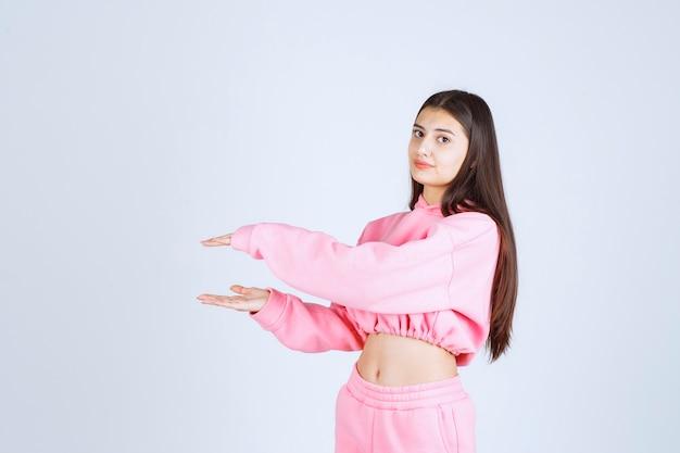 Девушка в розовой пижаме показывает размер объекта