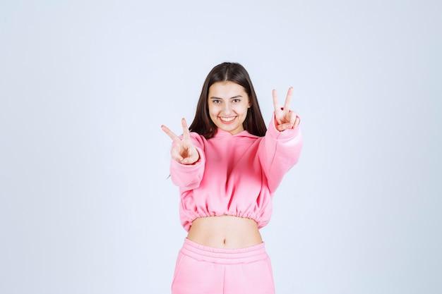 웃 고 뭔가 즐기는 분홍색 잠 옷 소녀.