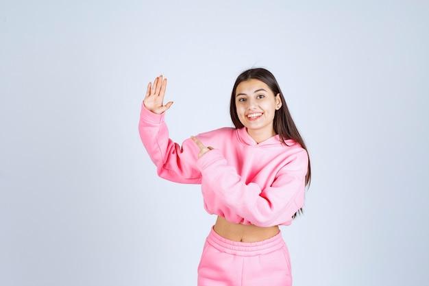 ピンクのパジャマを着た女の子が何かまたは誰かを止めている