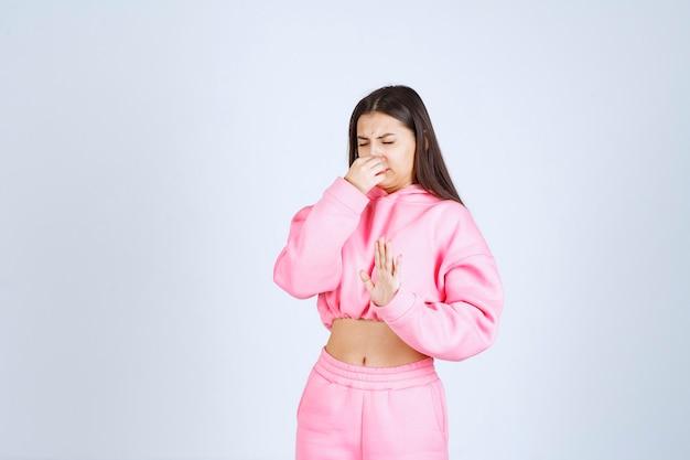 Девушка в розовой пижаме останавливает что-то или кого-то