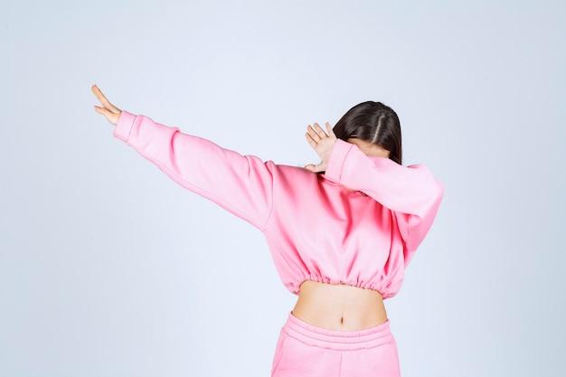 ピンクのパジャマを着た女の子が何かを止めている