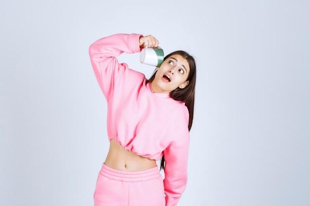 빈 커피 잔을 복용 분홍색 잠옷 소녀와 실망됩니다.
