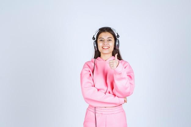헤드폰을 착용하고 즐거움 기호를 보여주는 분홍색 잠옷 소녀. 고품질 사진