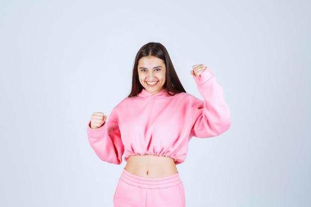 Девушка в розовых пижамах - победительница и показывает кулаки