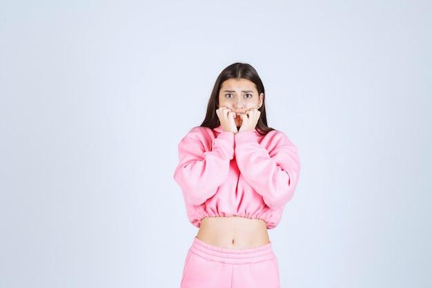 분홍색 pijamas를 입은 소녀는 무서워하고 겁에 질려 보입니다.