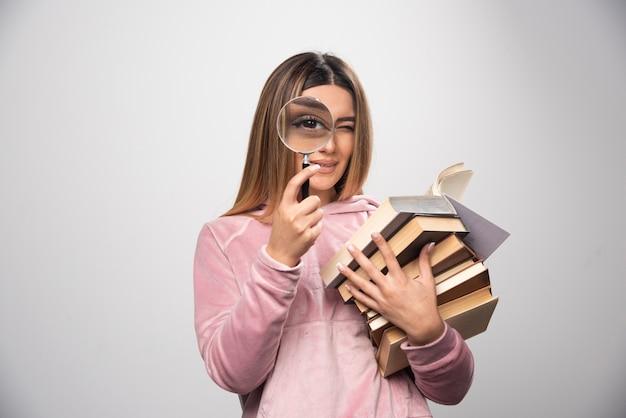 Девушка в розовой рубашке держит стопку книг и пытается прочитать верхнюю с лупой.