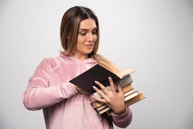 Девушка в розовой рубашке держит стопку книг, открывает одну сверху и читает