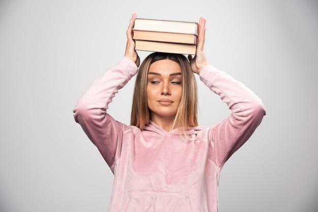 그녀의 머리 위에 그녀의 책을 들고 분홍색 swaetshirt에서 소녀.