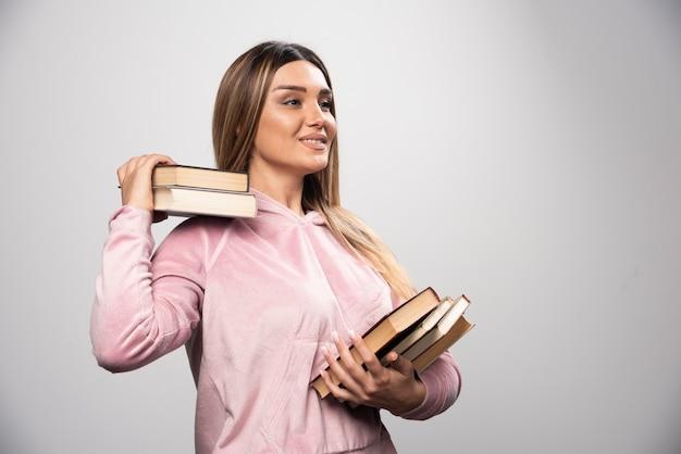 그녀의 어깨 너머로 그녀의 책을 들고 분홍색 swaetshirt에서 소녀.
