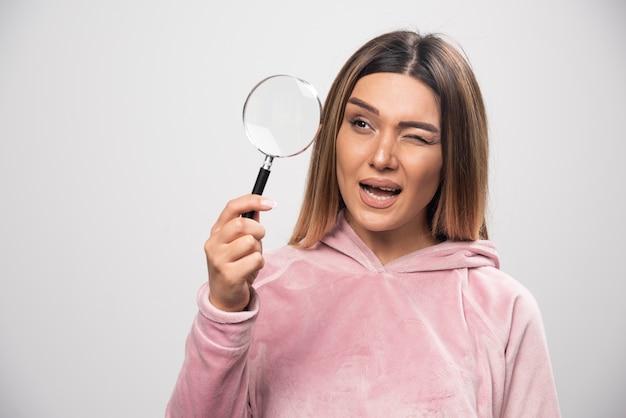 彼女の目に拡大鏡を置き、それを通して見ているピンクのswaetshirtの女の子。