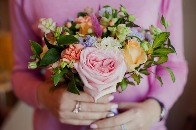 バラの美しい緑豊かな花束を保持しているピンクのセーターの女の子