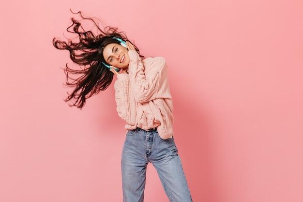 ピンクのセーターを着た女の子が音楽を聴き、髪の毛で遊んでいます。孤立した背景にうれしそうな女性のスナップショット。