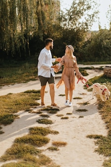폴카 도트 드레스를 입은 소녀와 카키색 반바지를 입은 남자 친구가 공원에서 커다란 흰색 개를 걷고 있습니다.